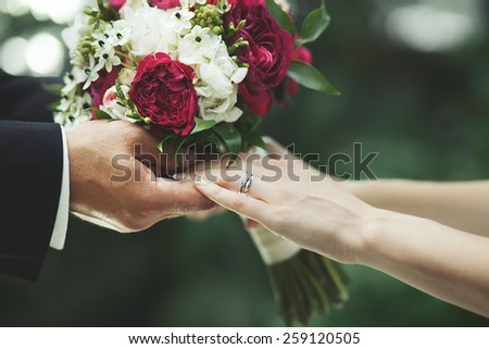 Newlywed couple holding hands, groom and bride together on wedding day. - stock photo