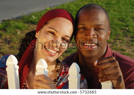 Newlywed couple holding on to a white picket fence, full of dreams and hopes for the life ahead - stock photo