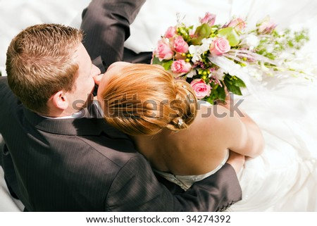 Newlywed couple hugging and kissing, the bride holding a bouquet of flowers in her hand - stock photo