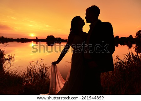 Newlywed couple hugging each other lovingly at sunset. - stock photo