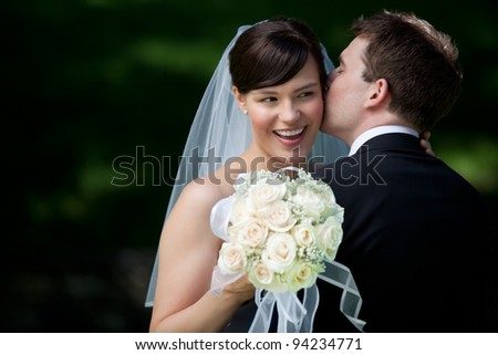 Newlywed Couple Kissing Each Other Holding Flower Bouquet In Hand. - stock photo