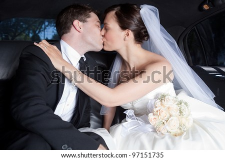 Newlywed Couple Kissing Each Other In Limousine. - stock photo
