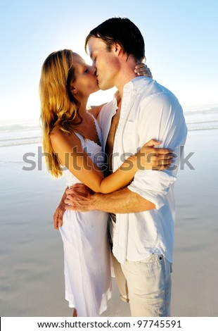 Newlywed couple kissing on honeymoon, beach vacation in summer and an intimate moment. - stock photo