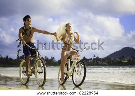 newlywed couple on the beach with their bicycles - stock photo