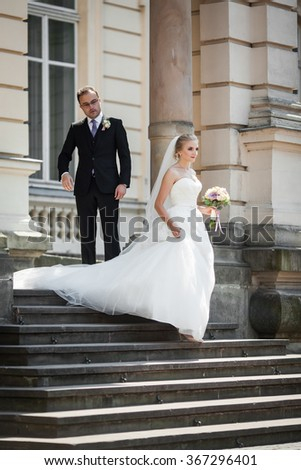 Newlywed couple posing near old building, bride walking down stairs