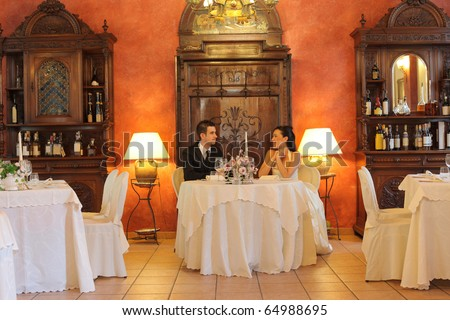 Newlywed couple sitting in a luxury restaurant - stock photo
