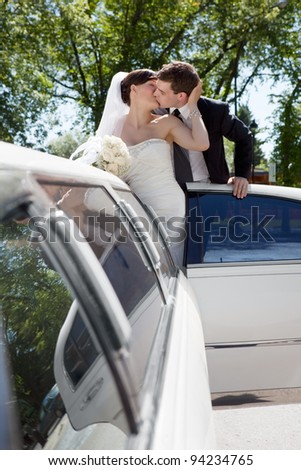 Newlywed Couple Standing Beside Limousine Car Kissing Each Other Holding Bouquet In Hand. - stock photo