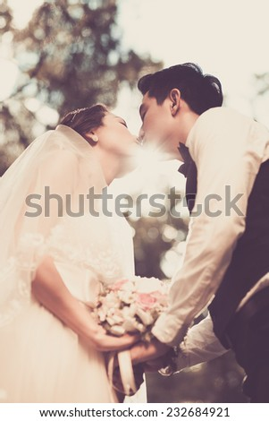 Newlywed couple tenderly kissing outdoors - stock photo