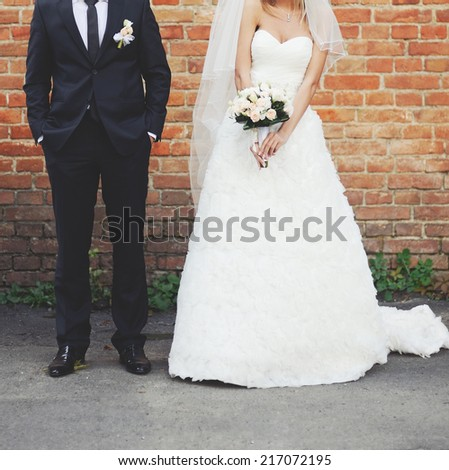 Newlywed couple together, posing against break-wall.  - stock photo