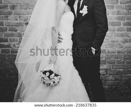 Newlywed couple together, posing against break wall.  - stock photo