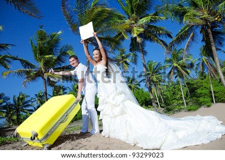 Newlyweds are hitchhiking at a tropical location - stock photo