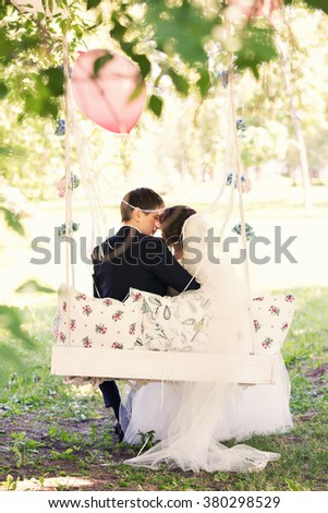 newlyweds embrace sitting in a swing outdoors - stock photo