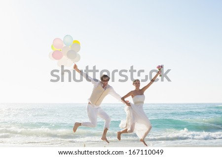 Newlyweds having fun holding balloons at the beach - stock photo
