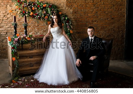 newlyweds in a beautiful room full of flowers. Bride stands at the chest. Bride sitting in a leather chair - stock photo