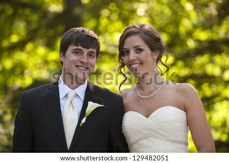 Newlyweds in an outdoor forest setting - stock photo