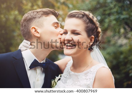 Newlyweds in love. The color photo of bride and groom are walking together in a park. The groom is kissing a bride. Bride is smiling with pleasure. Bride is happy.   - stock photo
