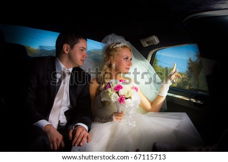 Newlyweds in the limo looking out the window - stock photo