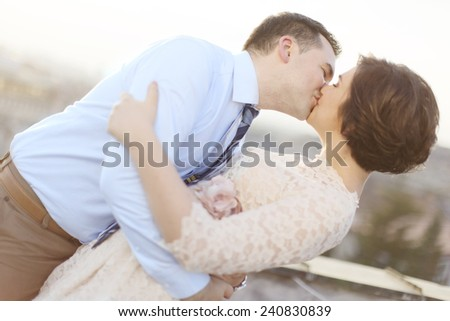Newlyweds kissing at the rooftop - stock photo