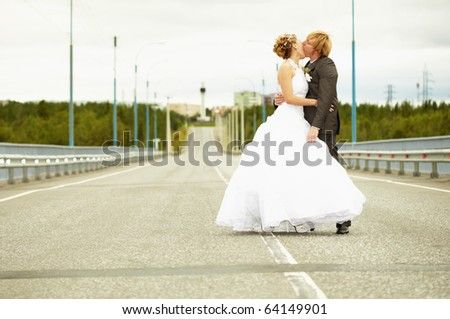 Newlyweds kissing passionately while standing on the highway - stock photo