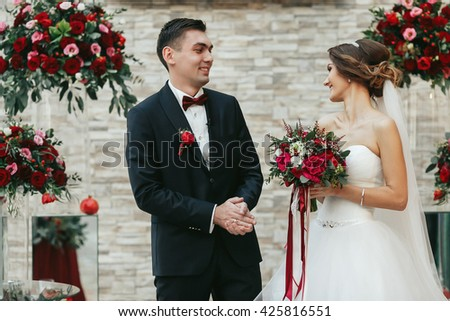 Newlyweds looking at each other joyfuly during the ceremony