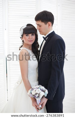 Newlyweds on a background of a white wall. Bride and groom. - stock photo