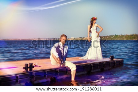newlyweds on a pier against blue water