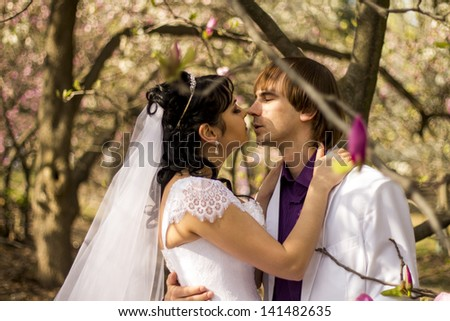 Newlyweds on nature background with blossoming magnolias - stock photo