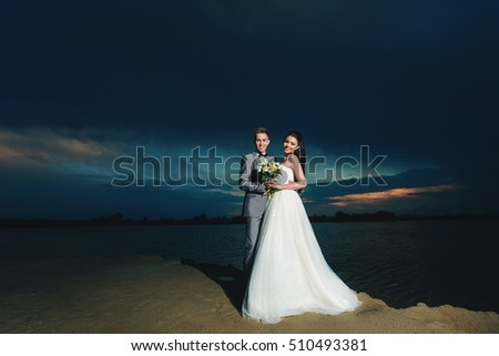 Newlyweds on the river bank at night