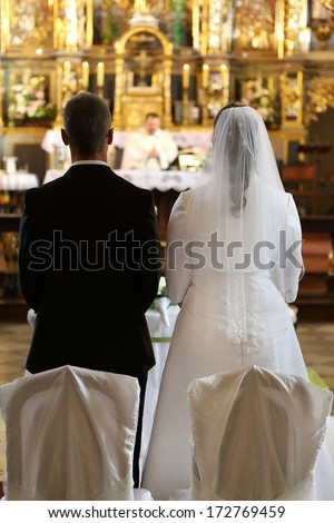 Newlyweds sitting in front of the altar during the wedding ceremony - stock photo