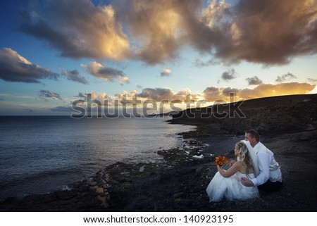 Newlyweds sitting in the ocean shore at sunset in Canary Islands.