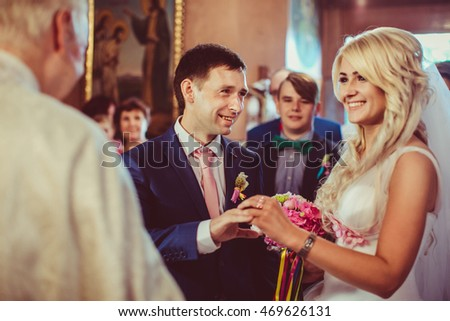 Newlyweds smile broad while putting wedding rings on each other fingers