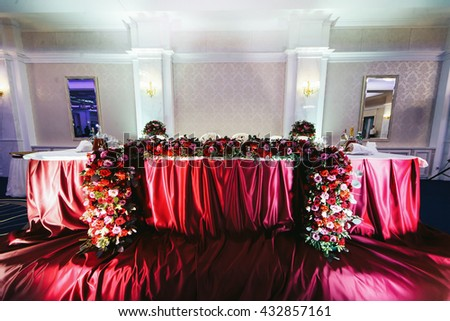 Newlyweds' table with the red silk cloth decorated with roses