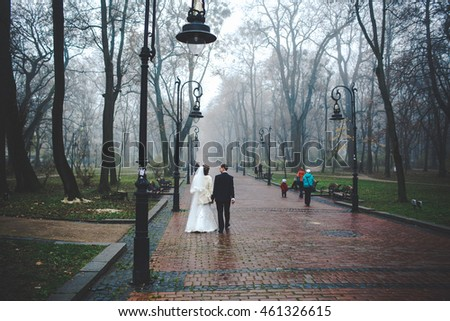 Newlyweds talk while walking under the lanterns in the foggy park