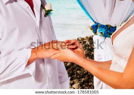 Newlyweds wear rings to each other on the background of the Caribbean. Groom put a ring on finger of his lovely wife. Wedding couple together. Closeup groom and bride hands in wedding ceremony - stock photo