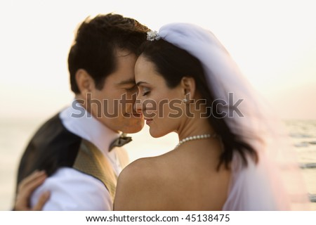 Newlyweds with their foreheads together affectionately on the beach. Horizontal shot. - stock photo