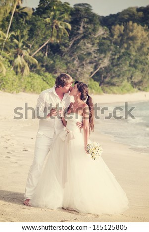 newlyweds with wedding bouquet of jasmine on the beach in the Seychelles - stock photo