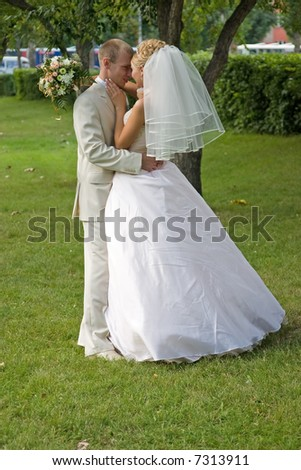 Newlywedses hug one another in park.