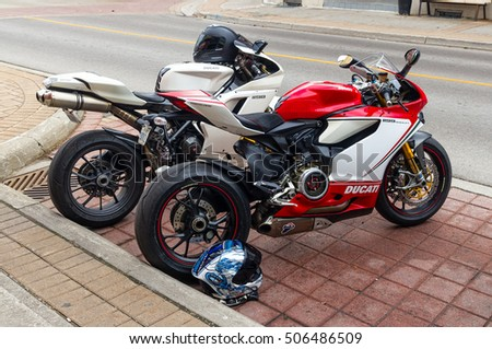 Newmarket, Ontario - Ooctober 29, 2016: Two powerful Ducati motorcycles in complentary colors are parked at the sidewalk.