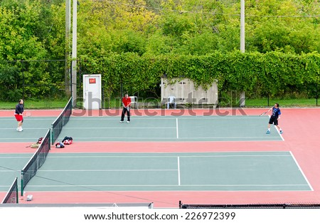NEWMARKET, ONTARIO - SEPT. 13, 2014: Group of senior citizens playing tennis on an asphalt court.