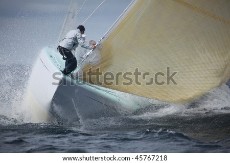NEWPORT, RI - SEPT 23: Foredeck crew finishes setting sail on the Courageous during 12 Meter World Championships in Newport, RI September 23, 2009. - stock photo