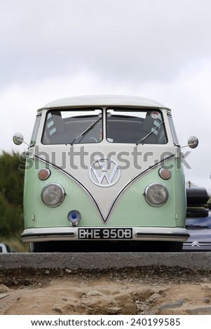NEWQUAY, ENGLAND - AUGUST 1, 2013: An old Volkswagen camper van parked in the Fistral Beach car park on August 1, 2013 in Newquay.  - stock photo