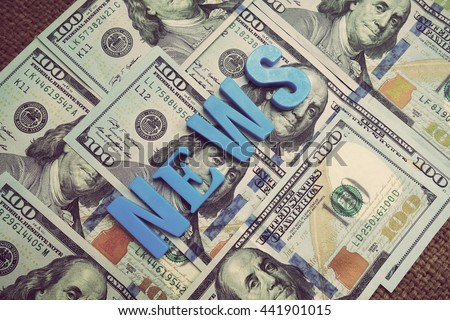 News concept. Blue letters on a background of US dollars