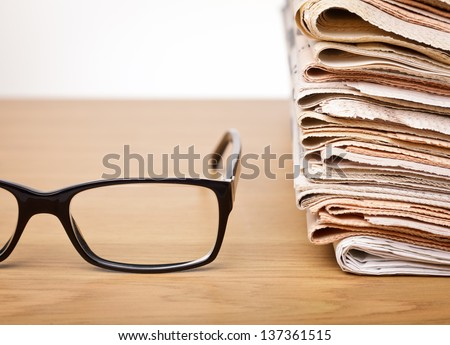 News concept �¢?? glasses on a table with stack of newspapers - stock photo