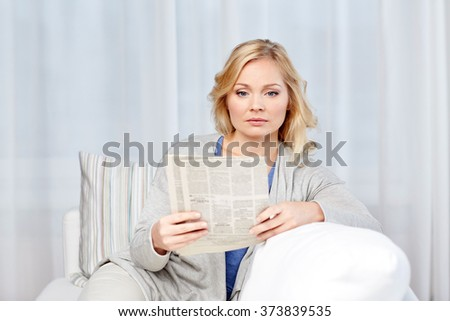 news, press, media, leisure and people concept - woman reading newspaper at home