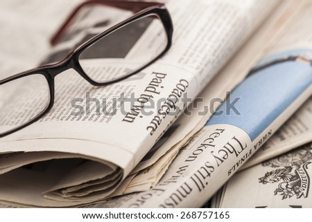 News. Reading glasses lie on newspaper pile - stock photo