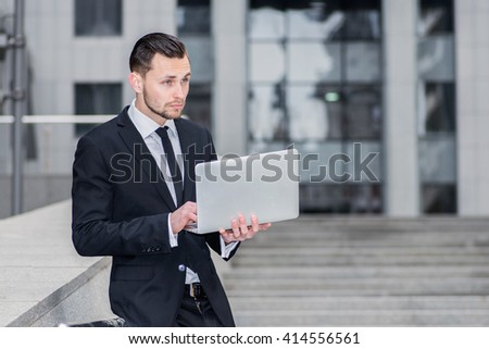 News Summary on the Internet. Confident businessman sitting on the steps and a laptop. Young man checks E-mail on the computer and drinking coffee.