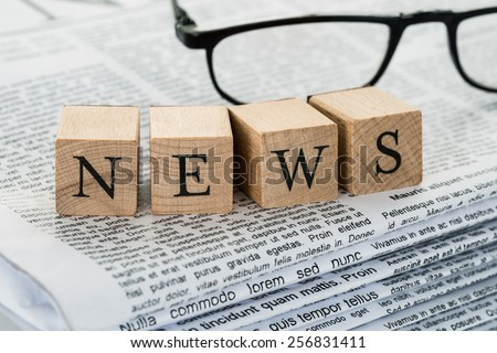 News Text On Wooden Blocks With Eyeglasses Over Stack Of Newspaper - stock photo