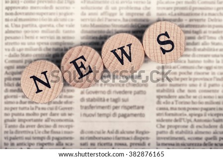 News text with wooden letters on a newspaper - stock photo
