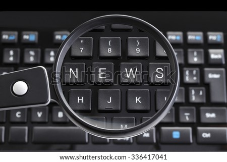 NEWS written on keyboard with magnifying glass