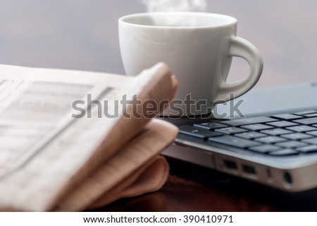 Newspaper and cup of coffee on wood table - stock photo
